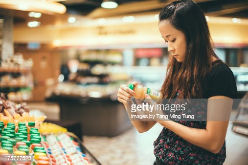 Young lady look at nutrition labels in supermarket
