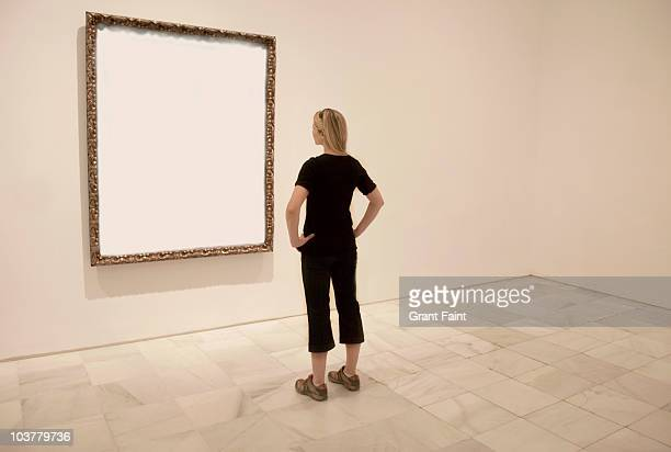 Young lady looking at blank art frame.