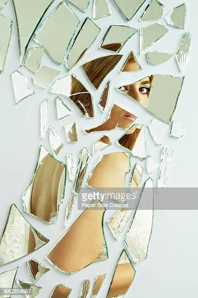 Young lady looking back at broken reflection