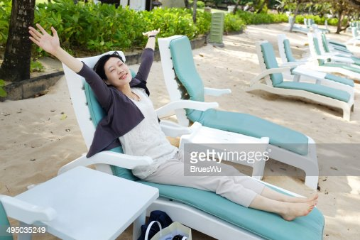 Young lady lying on loungers