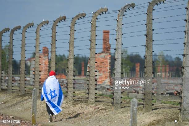 A young lady meditates as she walks near the barbed wire fence during the annual March of the Living inside the former German Nazi Death Camp...