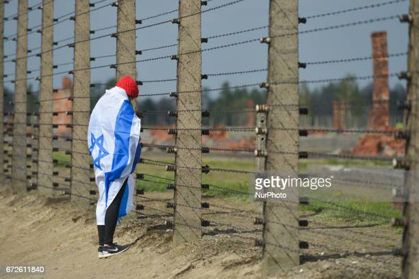 A young lady meditates at the barbed wire fence during the annual March of the Living inside the former German Nazi Death Camp AuschwitzBirkenau...