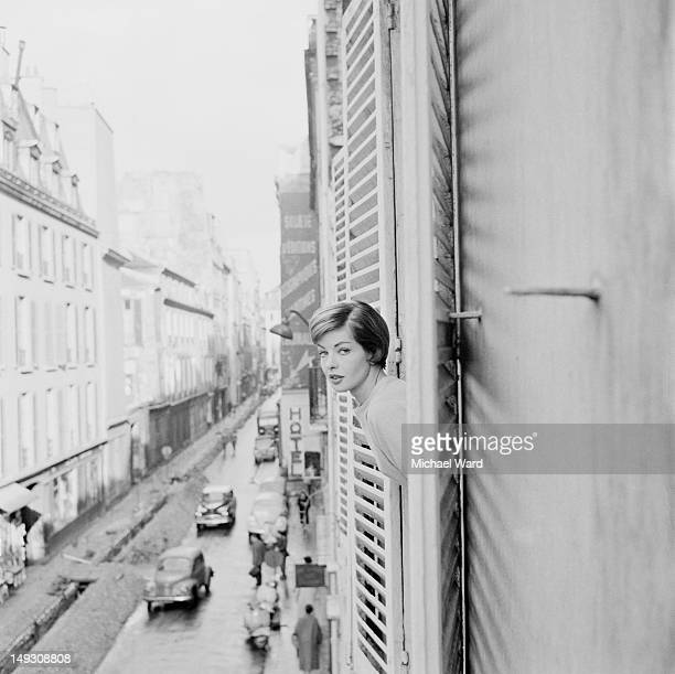 A young lady peers out of her hotel window in Paris 1959