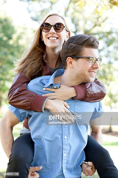 Young lady piggybacking on a man's back while both smile