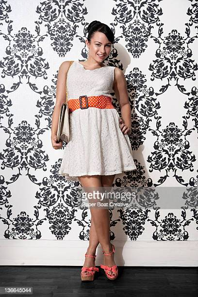 young lady posing against patterned wallpaper