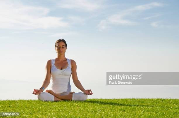 Young lady practising HathaYoga outdoor showing the pose padmasana lotus pose