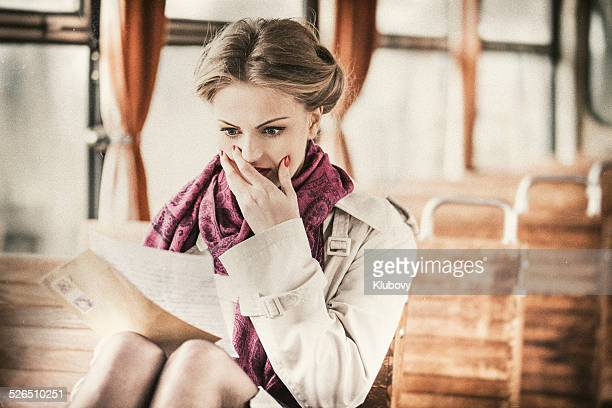 Young lady reading a letter in a vintage train wagon