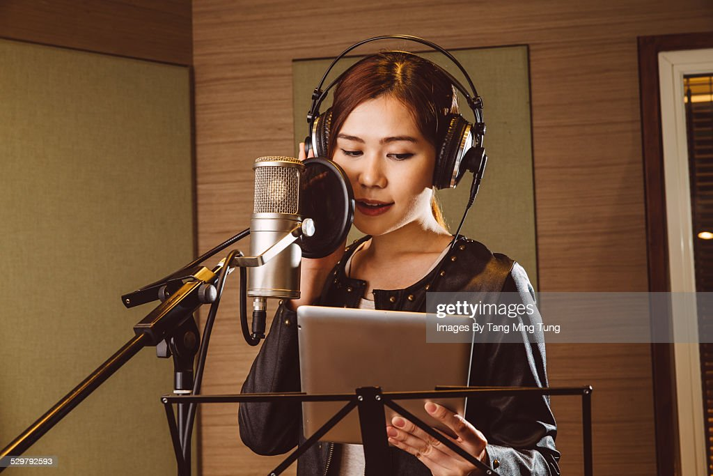 Young lady recording vocals in studio