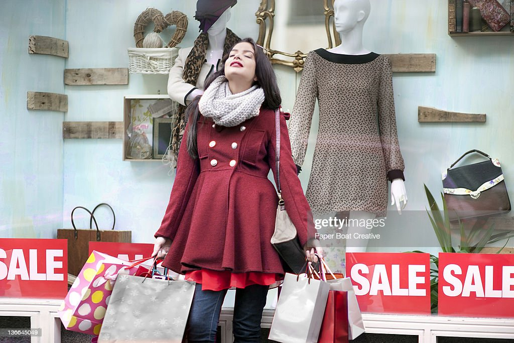 Young lady resting against a window shop : Stock Photo