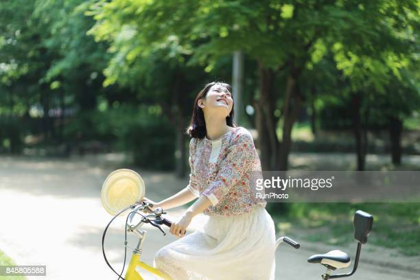 young lady riding a bicycle in the park