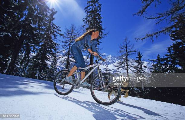 A young lady Riding her Mountain Bike with her pet dog.