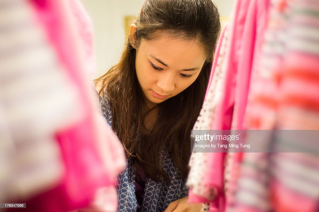 Young lady shopping for toddler's clothing : Stock Photo