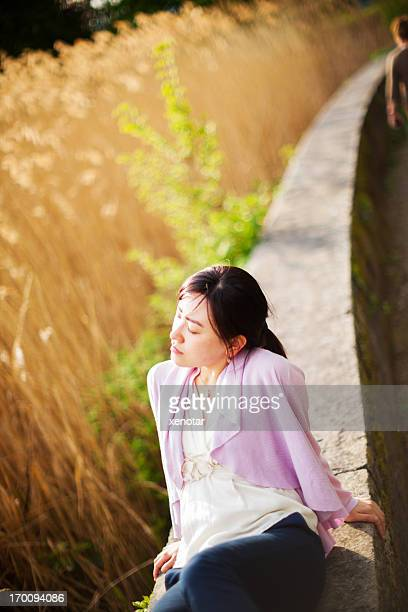 young lady sitting comfortable near grassland