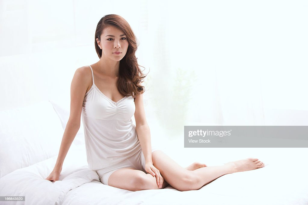 Young lady sitting on bed