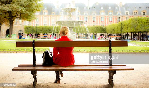 Young lady sitting on bench in Place des Vosges