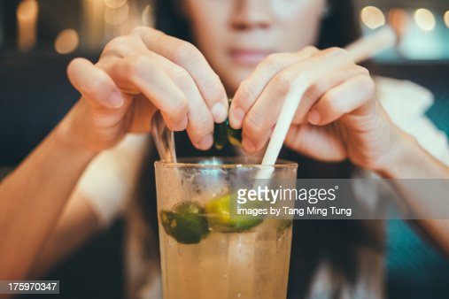 Young lady squeezing lime into a cold drink