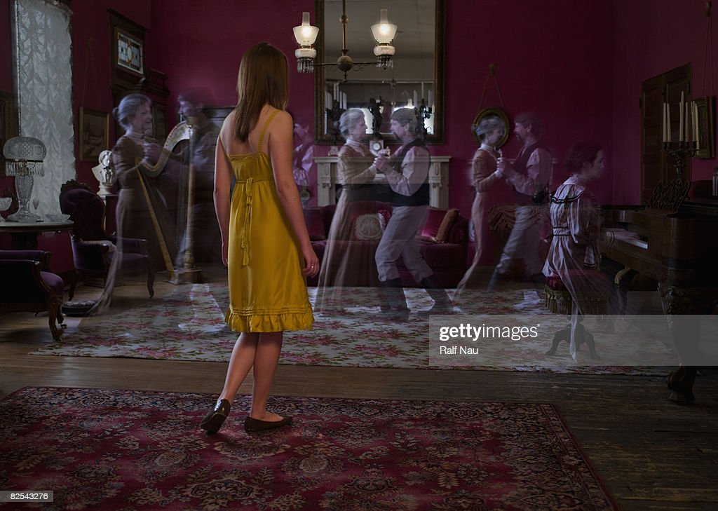 Young lady standing in parlor visualizing ghosts
