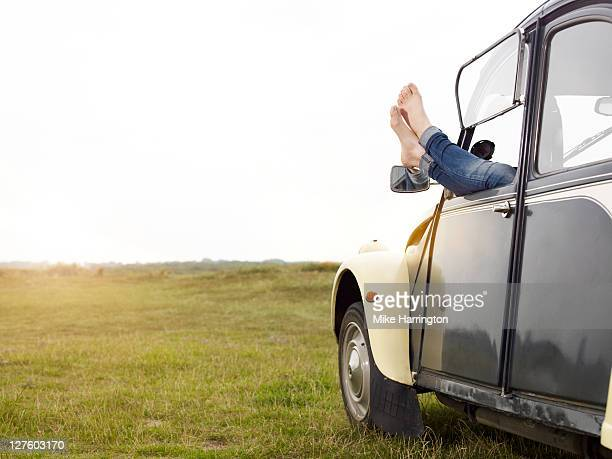 Young lady sticking feet out of car window