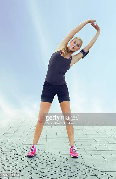 Young lady stretching her body by the walkway