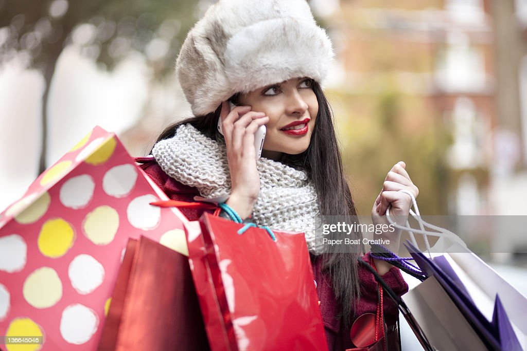 young lady talking on the phone while shopping : Stock Photo