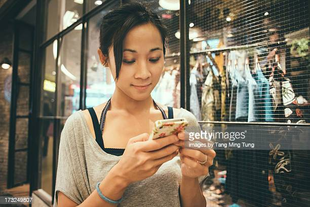 Young lady using smartphone in boutique.