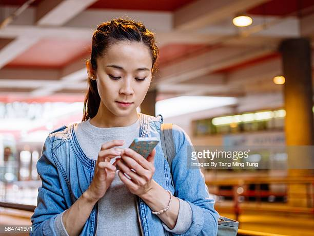 Young lady using smartphone in bus terminal
