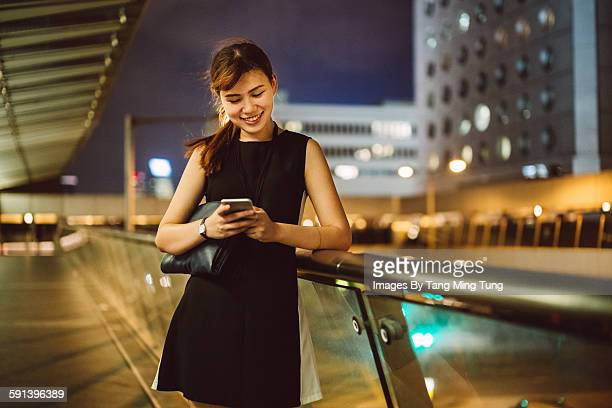 Young lady using smartphone in business district