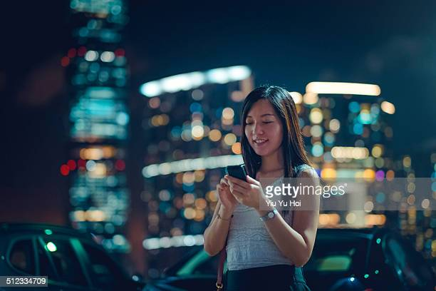 Young lady using smartphone in city street