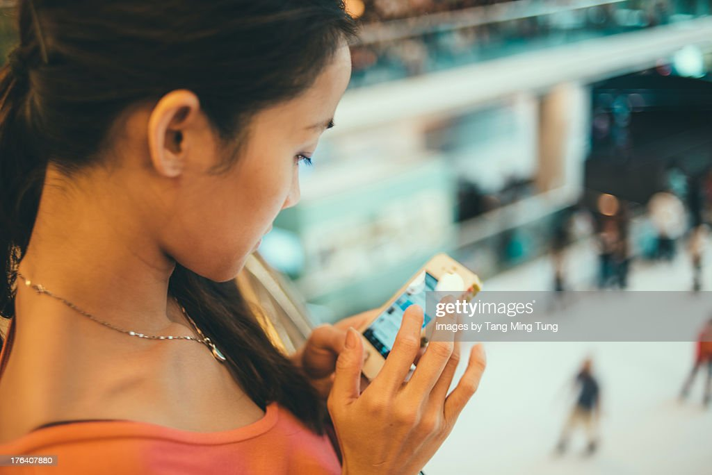 Young lady using smartphone in shopping mall.