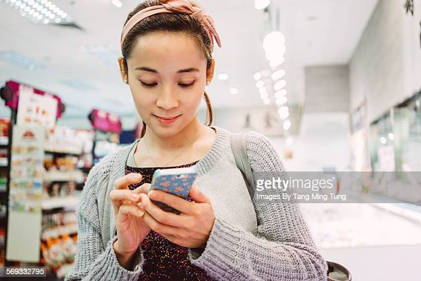Young lady using smartphone in supermarket