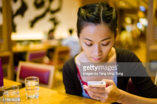 Young lady using smartphone in the restaurant : Stock Photo