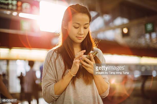 Young lady using smartphone on train platform