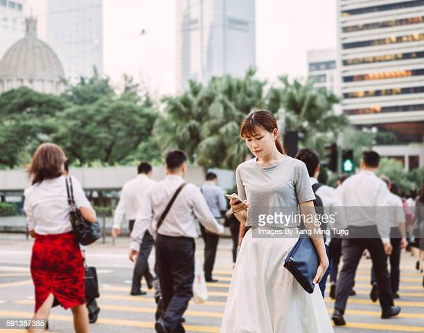 Young lady using smartphone while crossing road