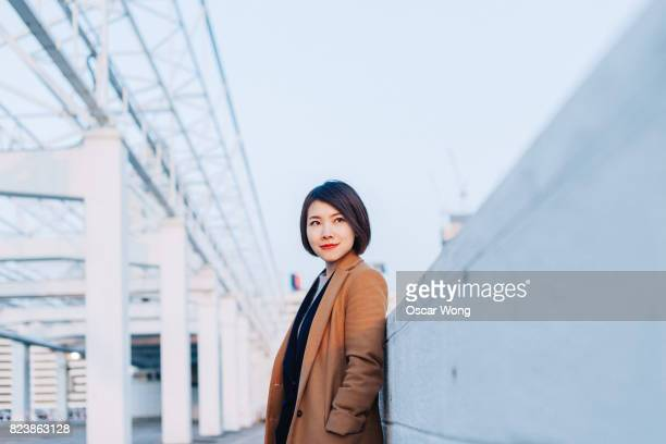 Young lady walking in harbour, against Hong Kong cityscape