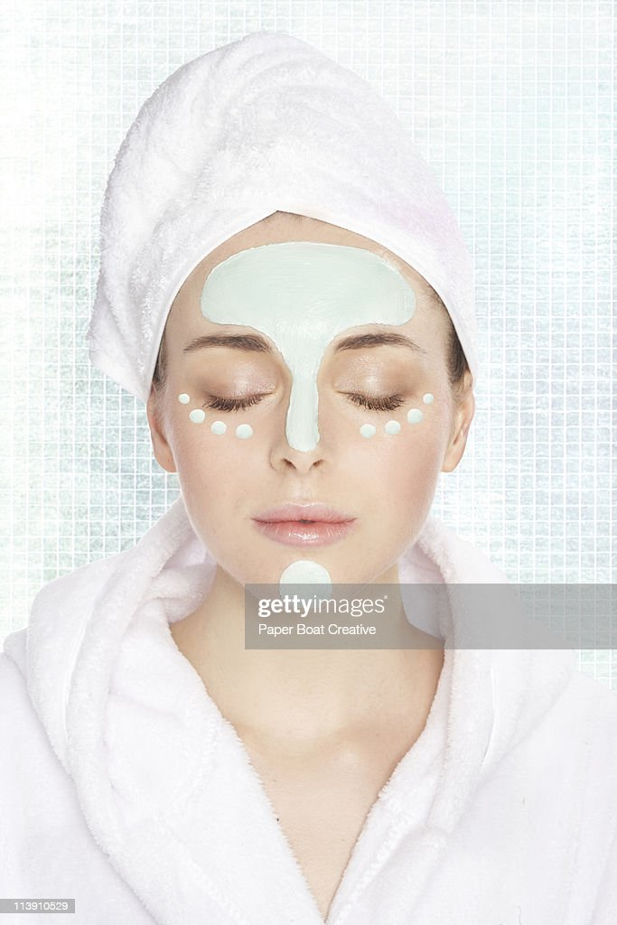 Young lady with green mud mask on her face : Stock Photo