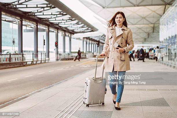 Young lady with luggage strolling at airport