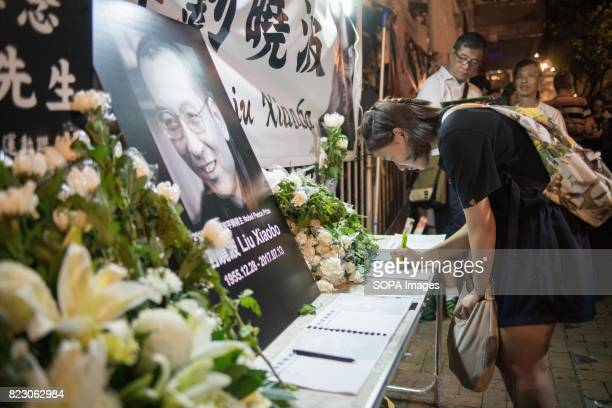 A young lady writing down words in the memorial book Residents of Hong Kong hosted a vigil service outside the Chinese Liaison Office of Hong Kong...
