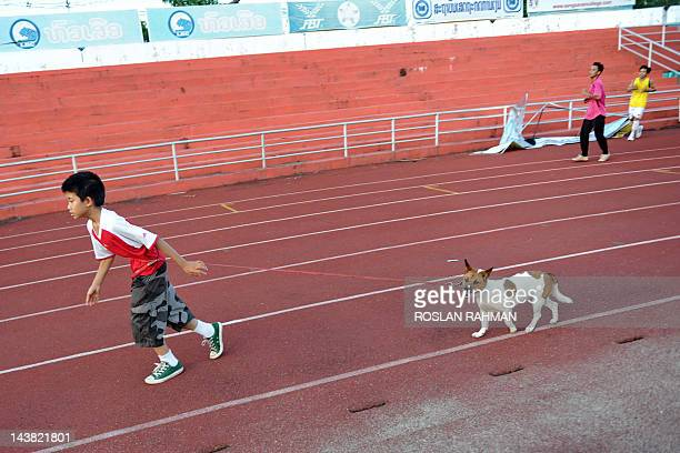 A young laotian boy jogs with his pet dog at a stadium in Vientiane on May 4 2012 The Lao government had targeted a GDP value of 70200 billion kip...