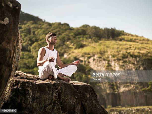 Young Latin American man meditating on a rock.