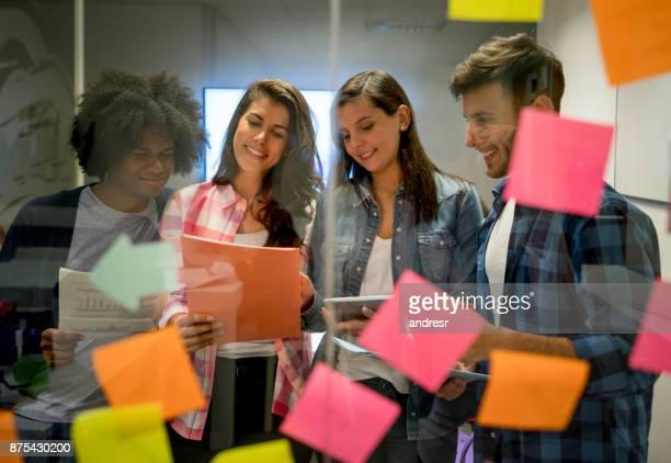 笑顔の事務所でアイデアに取り組んでいる若いラテン アメリカ多民族グループ