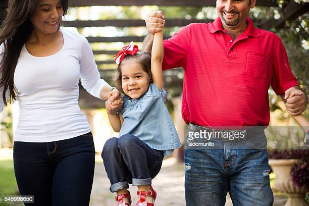 Young latin mother and father picking up little daughter