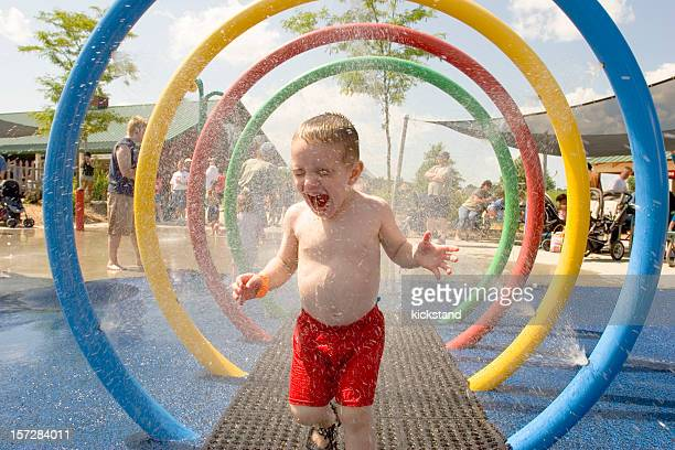 Young laughing boy runs through water park sprinklers