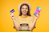 Young laughing female tourist holding credit card and passport with tickets, isolated on yellow background