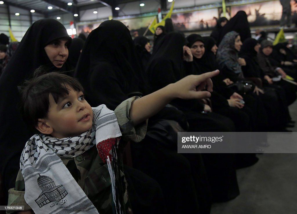 A young Lebanese boy attends with his mother a gathering called for by Hezbollah to mark the 'Al-Quds (Jerusalem) International Day' from Beirut's southern suburb neighbourhood of Rweiss on August 2, 2013. Hezbollah's chief Hassan Nasrallah made a rare public appearance at a Beirut rally held to mark Quds (Jerusalem) Day in support of the Palestinian people, an AFP photographer said.