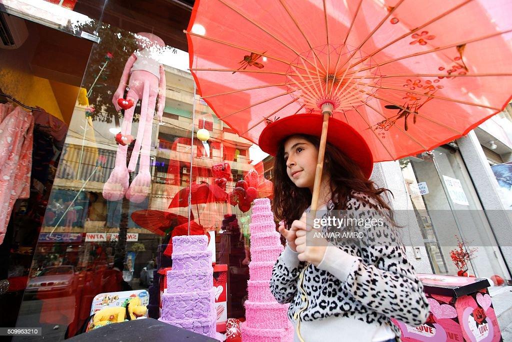 A young Lebanese woman walks with a red umbrella as she shops for Valentine's day gifts in the predominantly Shiite Muslim southern suburbs of the capital Beirut, on February 13, 2016. / AFP / ANWAR AMRO