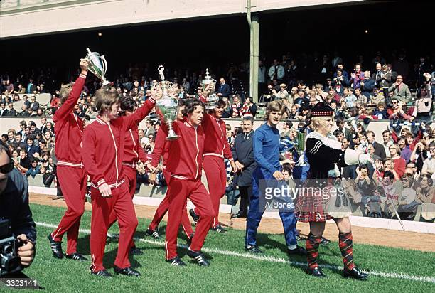 A young Liam Brady parades with other members of the Arsenal youth team carrying the Youth team FA Cup the League Championshipand the FA Cup trophies...