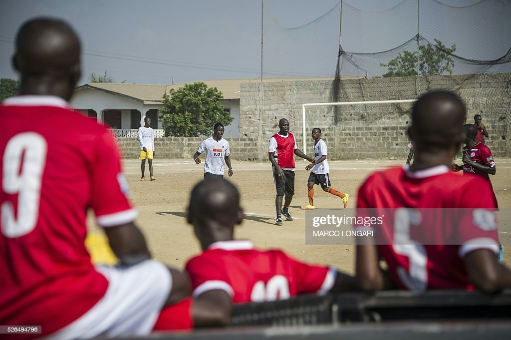 Young Liberian players look from the sideline as international Liberian soccer star, George Weah plays a match on a dusty pitch at the Alpha Old Timers Sports Association in Paynesville in Monrovia on April 30, 2016. Former international football star George Weah said on April 28, 2016, he would be a candidate in next year's presidential elections in Liberia, his second bid for the post. / AFP / MARCO