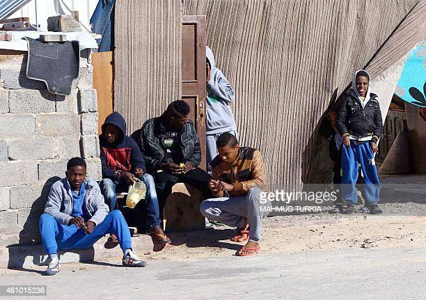 Young Libyans sit outside a makeshift house on January 4 2015 in the capital Tripoli at a refugee camp that hosts internally displaced people from...
