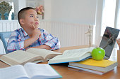 young little asian kid boy child children schoolboy thinking. childhood education