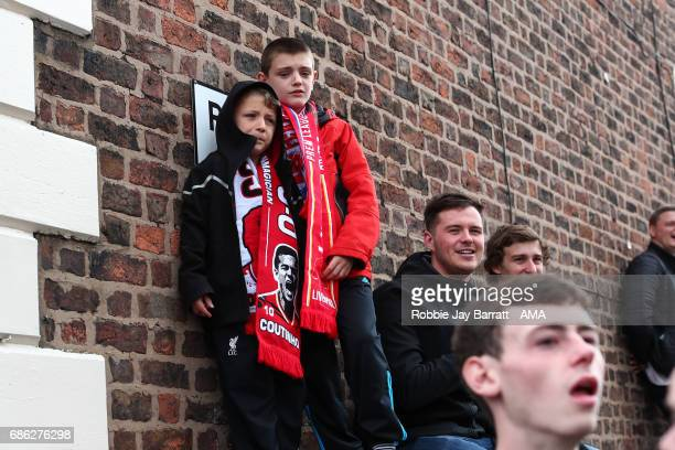 Young Liverpool fans wait for the team bus to arrive prior to the Premier League match between Liverpool and Middlesbrough at Anfield on May 21 2017...